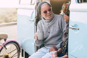 two happy seniors and mature married couple travelling together the worls with a blue and white van - sitting on the van with a cup of coffee or tea - elderly and retired travel lifestyle
