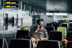 Lonely man sit down and use technology device like laptop and mobile phone at the airport gate waiting for his filght - concept of flights deleted and wait people - rights travel