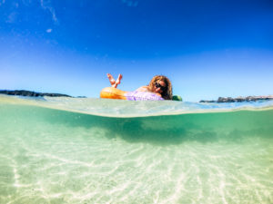 Cheerful tourist people young woman enjoying her trendy new inflatable mattress in the transparent sea water on a sandy beach during summer holiday vacation - travel and lifestyle concept