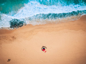 Aerial view of ocean waves and sand beach with tourists walking - summer holiday vacation concept with people - blue and yellow colors - tropical scenic place with nice nature and outdoors
