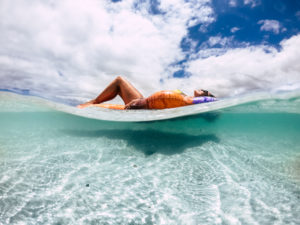 Beautiful tanned young woman lay down and relax on a trendy inflatable lilo in a paradise beach with sand and clear blue water - underwater and out image for vacation and travel concept lifestyle