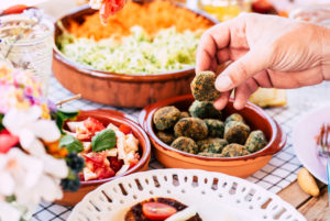 Close up of man taking polpetta in vegetarian food table - concept of market and catering restaurant for party or event