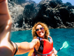 Cheerful people happy smiling female take selfie picture with kayak having outdoor leisure sport activity in the blue ocean water - concept of hapiness in summer holiday vacation