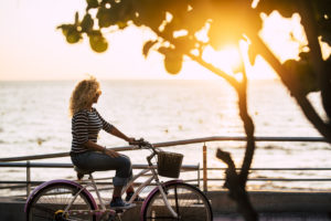 Inependent free woman enjoying the outdoor leisure activity riding a bike with sunset and ocean in background - concept of nice free lifestyle and vacation for lonely ladies