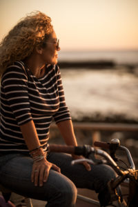 Beautiful adult caucasian woman looking at the sunset panorama sitting on a bike -enjoying and relaxing in outdoor leisure activity - happy relaxed people portrait