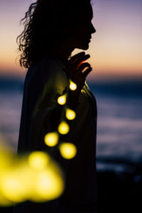 Silhouette of a woman holding a glowing string of lights, evening mood