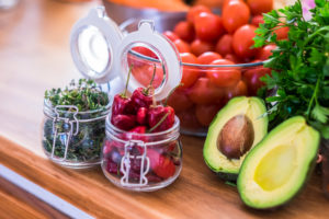 Healthy food with vegetables and fruit cloured on a wooden table - vegan or vegetarian nutrition concept - guacamole avocado trendy lifestyle health with tomatoes and red chilly pepper