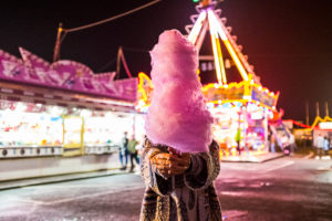 Hidden woman with pink strawberry cotton candy at night luna park - people have fun in nightlife at the event in the city