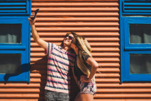 Young beautiful caucasian people couple take a slefie picture together with a kiss and smile - technology and social media pictures concept - coloured background