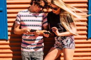 Young caucasian couple use modern cellular phone device together sharing contents with app and technology - outdoor people in leisure activity with internet and social media