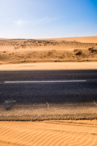 Black asphalt road with sand dunes and desert on left and right and blue sky in background  - travel concept in arid desertic world due a bad climate change future - water emergency planet
