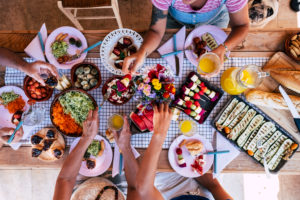 Top view of group of friends haveing fun together ina healthy vegetarian fresh seasonal brunch together - coloured and energetic food to eat with friends or family - people stay together at home or restaurant