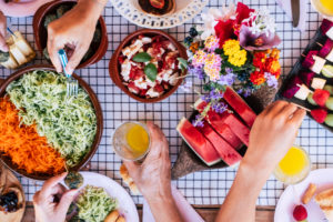 Top view of group of friends having fun together in a healthy vegetarian fresh seasonal brunch together - coloured and energetic food to eat with friends or family - people at home or restaurant