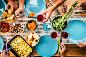 Top vertical coloured view of table full of food and colors - decorated and celebration concept with people eating together in party or event family and friends meeting