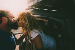 Adult couple in love kiss outside the car and travel together - concept of free and happy lifestyle for beautiful people traveling and enjoying life