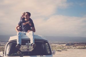 Love and travel with romantic wanderlust young people couple hug and stay together on an old vintage van rooftop enjoying romance and relationship - alternative tourist vacation lifestyle