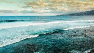 Aerial oceanand coastline view - sea water and surf waves and sky with clouds at the horizon in background - tourism and coast scenic place for vacation