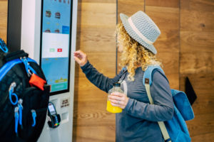 one adult woman choosing, her food in a restaurant or bar with a touch screen distributor in some fast food - curly lady choosing what to eat at luch or dinner