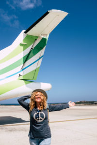 one happy beautiful woman having fun traveling enjoying her vacations outdoors discovering new places - portrait of adult person with airport or aircraft at the background