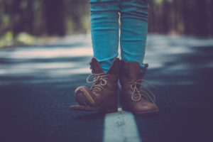 Concept of travel lifestyle for free people - money related concept and close up of woman legs with broken shoes on the road - walk and enjoy the adventure with asphalt and defocused background