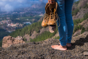 Travel and wanderlust lifestyle concept with barefoot woman stand up with broken shoes on hands looking at the view on the top of the mountain