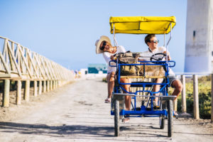 Mother and son have fun together enjoying a surrey bike in outdoor leisure activity or summer holiday vacation - active family people with different ages play and laugh like friends