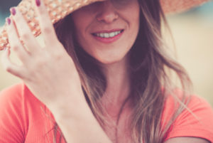 Close up woman portrait in vintage pink tones with cheerful and happy hidden eyes young caucasian lady with long beautiful hair and hat - concept of trendy people smile