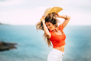 Happiness and joyful people concept with beautiful young woman portrait jumping and laughing a lot having fun - blue outdoor ocean in background and long hair
