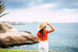 Tourism concept with beautiful female tourist viewed from back looking and enjoying the blue ocean and sky - summer holiday vacation and outdoor leisure activity