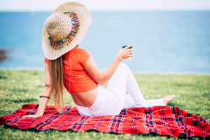 Summer and tourist concept with trendy caucasian woman sit down on the grass and enjoy looking the blue ocean drinking a tea or coffee alone - coloured lifestyle and travel