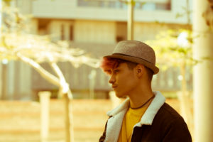 Yellow old style mood filter colors portrait of young handsome alternative male teenager man in the city with urban background
