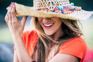 Smile and perfect teeth beautiful young woman laughing and enjoying outdoor - trendy hat and fashion caucasian female portrait - happiness and joyful people concept lifestyle