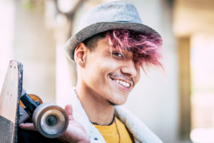 Portrait of handsome cheerful young man teeanger boy smile and look at the camera - modern people with alternative look and coloured hair - skateboard and hat on man