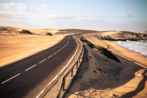 Long black asphalt road with desert and beach around for travel and adventure summer lifestyle concept with nobody traveling and no traffic cars - beautifful adventure places to discover