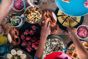 Close up vertical view of table and caucasian hands taking food to eat and celebrate together in friendship - people friends have fun and eat meat on a wooden table