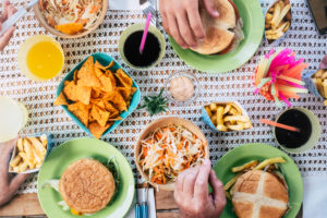 Vertical table view with people eating junk hamburger food together - home scene and friendship at lunch concept