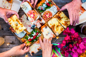 Close up view of table full of caucasian group people hands taking italian pizza and eat together in friendship for celebration party - concept of happiness and friends at home or restaurant