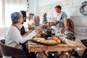 Family enjoy together christmas lunch at home - caucasian people have fun in friendship celebrating holidays and eve - white home and wooden style table