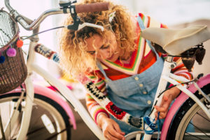 Happy adult woman at home in hobby work leisure activity indoor modify a female bike with piece of covers and full of colors - creativity concept and hippy boho bicycle creation - people enjoying artistic job at home