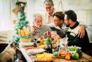 Cheerful caucasian family enjoy and celebrate together at home with table full of christmas decorations - mixed ages and generations from teenager to senior and adult have fun
