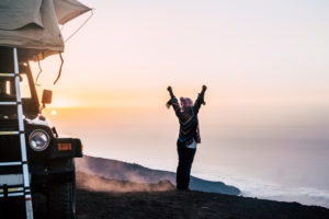 Happy joy people travel with car and tent roof in wild places enjoying the sunset on the top of a mountain - travel and freedom lifestyle concept for young woman