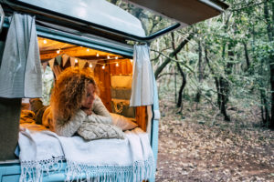 Happy free beautiful woman lay down and relax inside her blue van vehicle parked in the forest - people enjoying alternative travel and vacation or life options - female enjoying the camper van vacation
