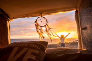 Travel and freedom concept with standing happy joy woman outside vehicle van enjoy the sunset at the beach - dreamcatcher in foreground and sun in background