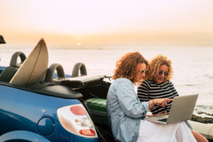 Young and beautiful middle age woman enjoy travel and technology roaming with car and sunset in background - people with laptop computer outdoor in vacation leisure activity time