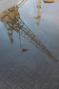 old cranes in the museum harbor reflecting in a puddle