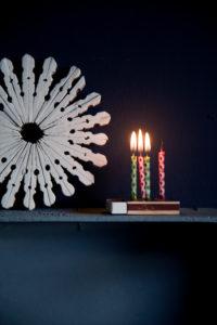 Winterdekoration mit brennenden Kerzen auf Streichholzschachtel,