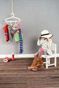 Girl sits on a chair in the wardrobe and wears the shoes of the mother,