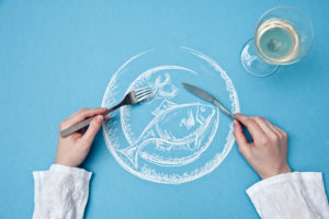 drawing of a fish plate, bird's-eye view, A person holds knife and fork over the plate,