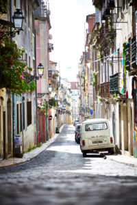 View along a street, alley in town, parking cars, Volkswagen Bus, Lisbon, Portugal