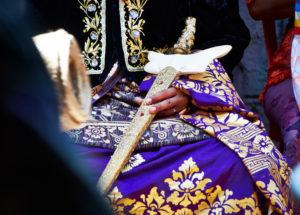 Bräutigam in Festkleidung, sitzt, Close-up, Schwert, aufwendig geschmückt, Gold, Stickereien, Reportage, traditionelle Hochzeit, Bali, Indonesien, Asien